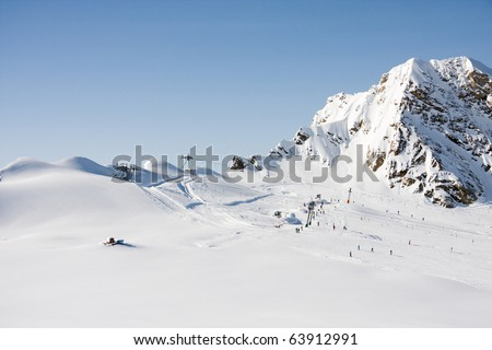 Alps mountains and ski lift in sunny winter day