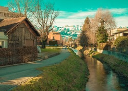 Alps mountains in Liechtenstein. Medieval Red House, calm narrow mountain river and jogging track, on the background of residential buildings, blue sky and snow-capped mountains. Liechtenstein, Vaduz