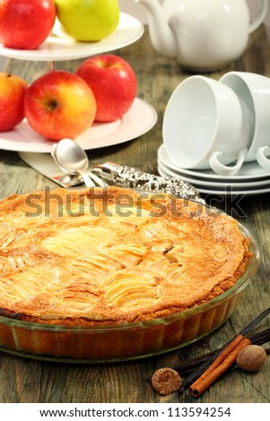 Alsatian apple pie and cup of tea on a wooden table.