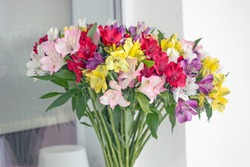 Alstroemeria bouquet of flowers in a vase by the window. Beautiful bouquet of colorful flowers in the apartment by the window.