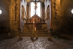 Altar in old church ossuary with human skulls and bones on walls, Kutna Hora, Czech Republic.