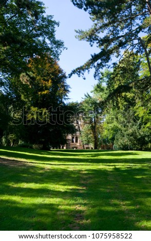 """Altenburg / Germany: View over the green meadow in the small """"Schmidtscher Park"""" to an impressive historical villa from the 1880s that is used as a schoolhouse today"""