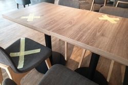 Alternate seating sign in a cafe, keep spaced between each chairs make separate for social distancing to avoid spreading of Covid-19.