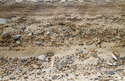 Alternation of layers of sand and gravel in a sediment near the coast