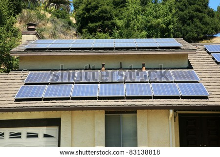 alternative energy photovoltaic solar panels on the roof of a home. collecting energy from the sun and helping save the earth from global warming and reducing their electric bills at the same time