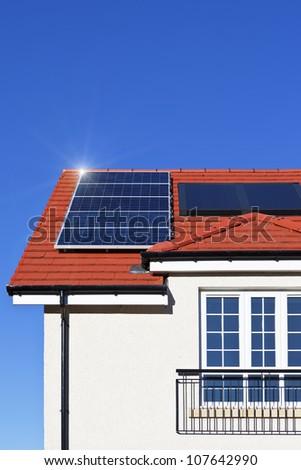 Alternative energy photovoltaic solar panels on tiled house roof