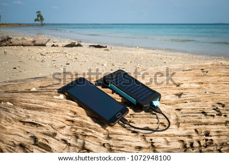 Alternative energy source. battery is charged by solar energy. Charging mobile devices in the wild. island beach. Powerbank charges the phone on the background of palm trees and sandy beach #1072948100