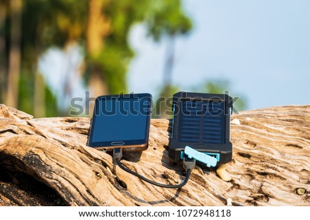Alternative energy source. battery is charged by solar energy. Charging mobile devices in the wild. island beach. Powerbank charges the phone on the background of palm trees and sandy beach #1072948118