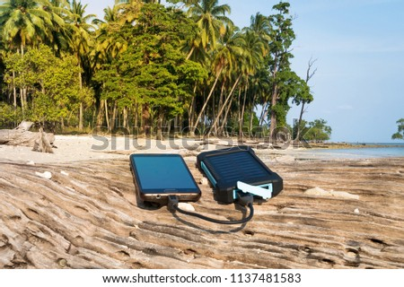 Alternative energy source. battery is charged by solar energy. Charging mobile devices in the wild. island beach. Powerbank charges the phone on the background of palm trees and sandy beach #1137481583