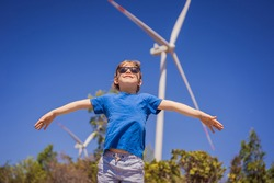 Alternative energy, wind farm and happy time with your family. Happy boy on vacation and escape to nature