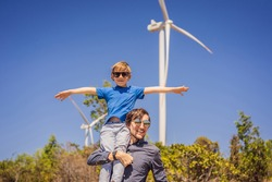 Alternative energy, wind farm and happy time with your family. Happy father carrying his son on shoulders is on vacation and escape to nature. Father carrying son on shoulders and waving their arms