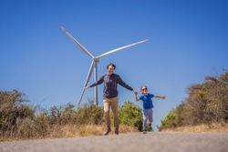 Alternative energy, wind farm and happy time with your family. Happy father on the road with his son on vacation and escape to nature. Father and son waving their arms like a windmill
