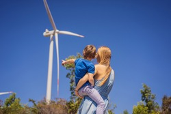 Alternative energy, wind farm and happy time with your family. Happy mother carrying his son on vacation and escape to nature