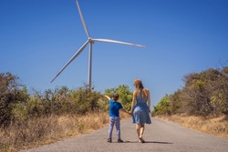 Alternative energy, wind farm and happy time with your family. Happy mother on the road with his son on vacation and escape to nature. Mother and son waving their arms like a windmill