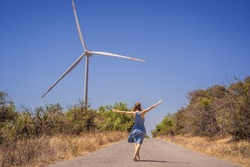 Alternative energy, wind farm and happy time with your family. Happy woman on the road on vacation and escape to nature