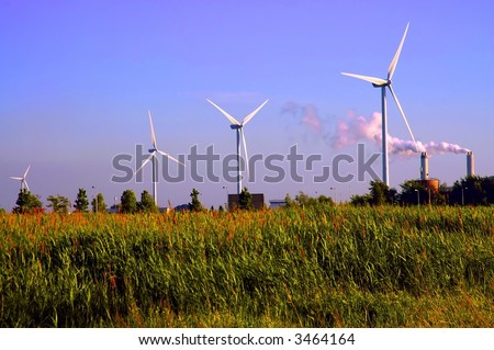 alternative energy wind turbines by the two smoking pipes of the factory
