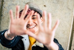 Alternative happy and cheerful diverse teenager hide his face and smile with hands in front of the camera composition - concept of diversity and trendy generation z boy in the city urban background