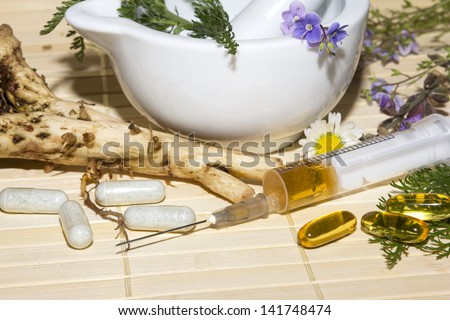 Alternative medicine and herbal extracts still life with a porcelain pestle and mortar with fresh medicinal herbs, flowers and roots with capsules and a syringe containing the extracts in front