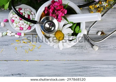 Alternative medicine herbs, berries and stethoscope on wooden table background Foto stock ©