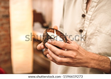 Alternative medicine man healer standing holding candle in coconut shell in salon close-up