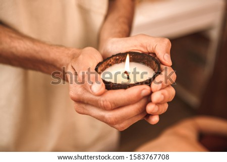 Alternative medicine man healer standing holding candle in coconut shell in salon close-up with two hands