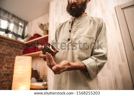Alternative medicine man healer standing holding candle in coconut shell in salon pouring wax on palm close-up bottom view