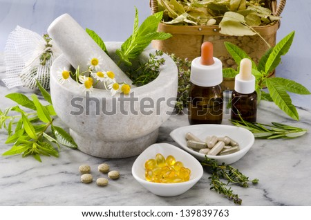 Alternative Medicine. Rosemary, mint, chamomille, thyme in a marble mortar. Essential oils and herbal supplements. Foto stock ©