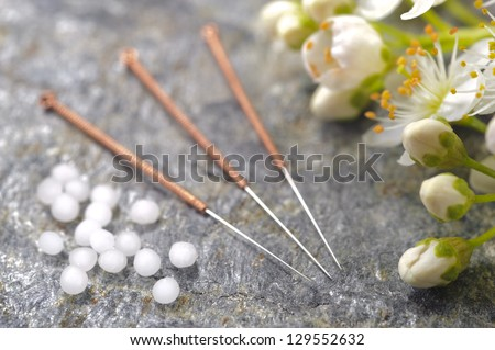 alternative medicine with homeopathic herbal pills and acupuncture needles