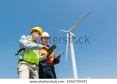 Alternative or Renewable Energy Technology Project Development Concept, Engineer and Architect discuss over Digital Wireless Tablet and Clipboard while working at Wind Turbine Power Generator To
