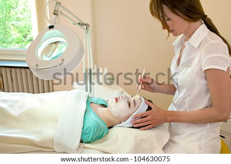 Alternative practitioner applying a chemical peel to a female patient's face in a beauty clinic
