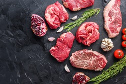 Alternative raw beef steak cuts with top blade, chuck roll and rump steak, with herbs and pomegranate top view, space for text