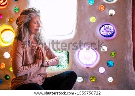 Alternative relaxed caucasian woman meditating and relaxing at home in yoga balance position -  artistic wall with coloured glass in background