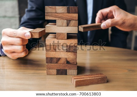 Alternative risk concept, plan and strategy in business, Young intelligent businessman playing the wood game, hands of executive cooperate placing wood block on the tower, Collaborative management.