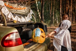 Alternative safe celebration. Cute kids celebrating Halloween party in the trunk of car with spider net, ghosts, carved pumpkin in medical mask for fun and other decoration, autumn outdoor