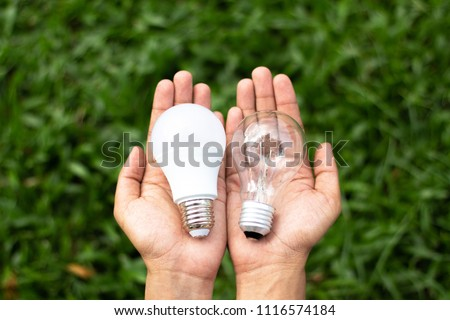 Alternative technology concept . Hands holding LED Bulb and Fluorescent bulb comparing in hands . copy space for text . Сток-фото ©
