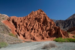 Altiplano. The arid desert and colorful mountains. View of the hiking path across the canyon. The orange sandstone and rocky formation part of Los Colorados in Purmamarca, Jujuy, Argentina.