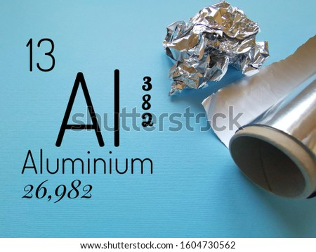 Aluminium - Aluminum is a chemical element with the symbol Al and atomic number 13. The symbol Al with atomic data (atomic number and atomic mass) and roll of silver aluminium foil in the background.