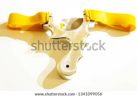 Aluminium Catapult Slingshot on a white background with gold bands. Shooting cartoon bad boy weapon
