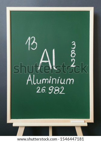 Aluminium - element of the periodic table. Symbol for the chemical element aluminium with atomic data (atomic mass, atomic number and electron configuration) written on green chalkboard.