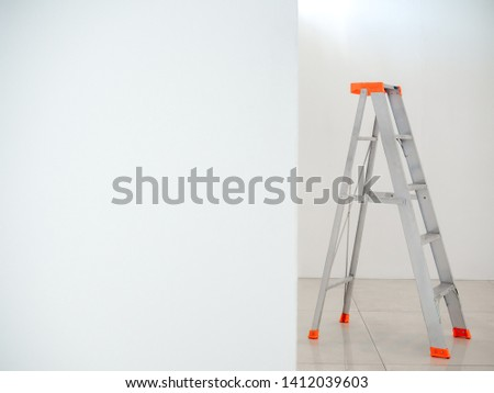 Aluminium folding ladder. Step ladder on white wall background with copy space. #1412039603