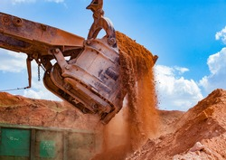 Aluminium ore quarry. Bauxite clay open-cut mining. Loading an ore to rail hopper car with excavator. Close-up of excavator bucket on blue sky with clouds.