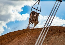 Aluminium ore quarry. Bauxite clay open-cut mining. Walking drag-line excavator bucket and steel cables and chains. On blue sky with clouds