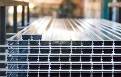 Aluminium profiles placed in a row inside an aluminium profile factory.