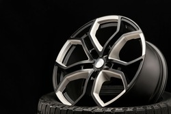 aluminum alloy wheel. Premium cast, the design of the spokes and the wheel rim, a white and black elements on dark background close-up