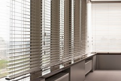 Aluminum blinds. Made from metal. Venetian blinds closeup on the window. Silver color. City landscape is in the background.