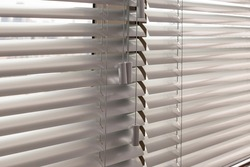Aluminum blinds. Made from metal. Venetian blinds closeup on the window. Silver color. Closed horizontal blinds in sunny day.