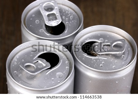 aluminum cans with water drops on brown background