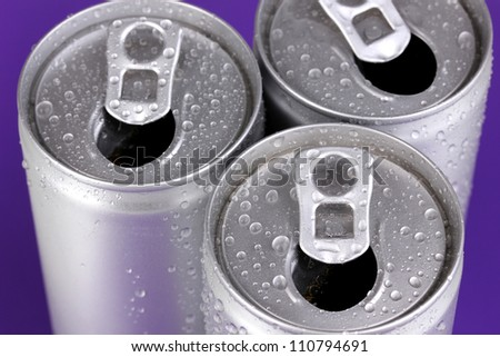aluminum cans with water drops on purple background