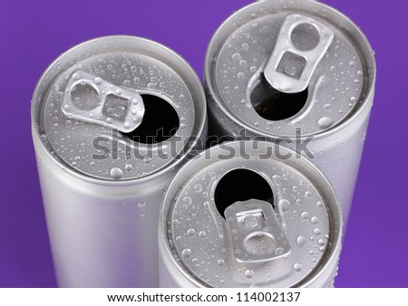 aluminum cans with water drops on purple background - stock photo