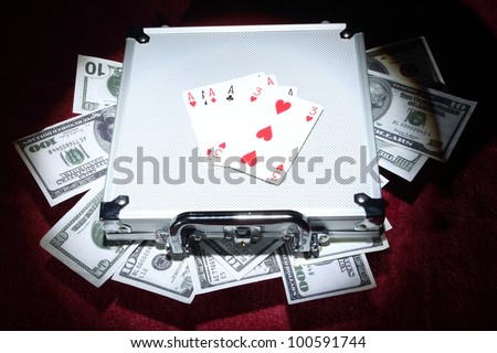 aluminum case with money and playing cards under the spotlight